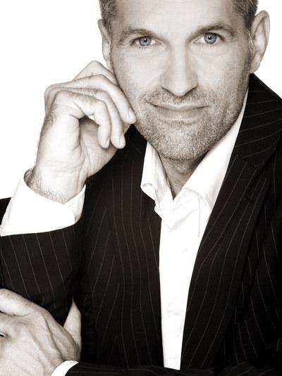 Portraitfoto von Karsten Windfelder. Karsten trägt ein weisses Hemd und einen dunklen Anzug. Sympathisches Laecheln.  Quelle: karsten-windfelder.de